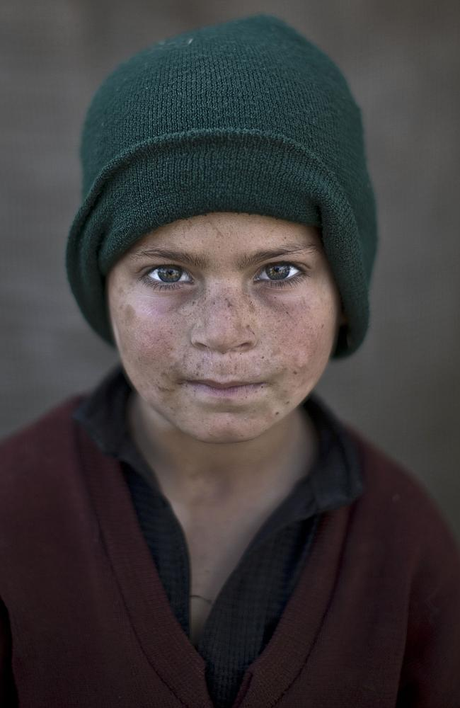 Afghan refugee boy, Hazrat Babir, 7, poses for a picture, while playing with other children in a slum on the outskirts of Islamabad, Pakistan.