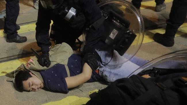 Police detain protesters after charging at them near the China Liaison Office after a protest against what activists say is police violence in Hong Kong.
