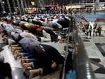 Muslim men offer prayers at the Kuala Lumpur International Airport for the missing Malaysia Airlines jetliner MH370, while on a level down, travellers queue up at immigration checkpoints. Picture: AP Photo/Wong Maye-E