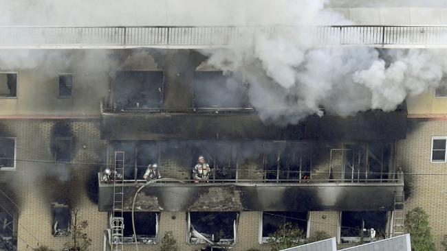 Firefighters work as smoke billows from the Kyoto Animation building in Kyoto. Picture: Kyodo News via AP