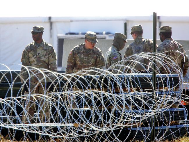 Military personnel stand behind bared wire as U.S. Secretary of Defence James Mattis visits Base Camp Donna on Wednesday, Nov. 14, 2018, in Donna, Texas. (Joel Martinez/The Monitor via AP)