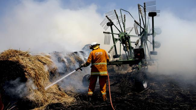 CFS volunteers tackle the fire in hay bales on a property at Mount Torrens in the Adelaide Hills. Picture: AAP / Kelly Barnes