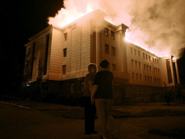 Bystanders watch a fire consuming a school in downtown Donetsk yesterday after being hit by shelling. Picture: Francisco Leong