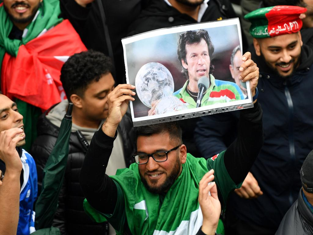A pakistan fan holds up a picture of Pakistani Prime Minister Imran Khan as rain delays play ahead the 2019 Cricket World Cup group stage match between Pakistan and Sri Lanka at Bristol County Ground in Bristol, southwest England, on June 7, 2019. (Photo by Saeed KHAN / AFP) / RESTRICTED TO EDITORIAL USE