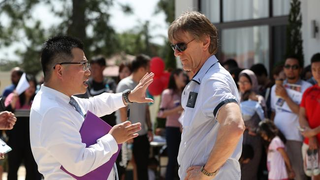Place agent Kevin Chiu speaking with Jeff Horn's trainer Glenn Rushton during the auction. Picture: Tara Croser.
