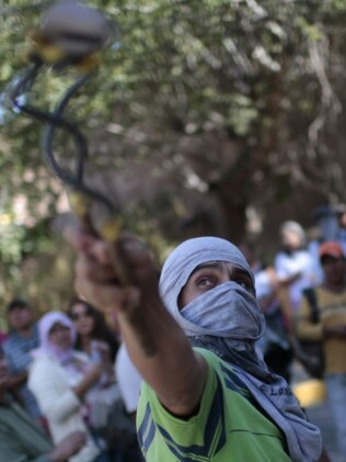 A teacher throws stones at the building of the lawyer of the Mexican state of Guerrero, during a protest a year after the disappearance of 43 students. Picture: AFP