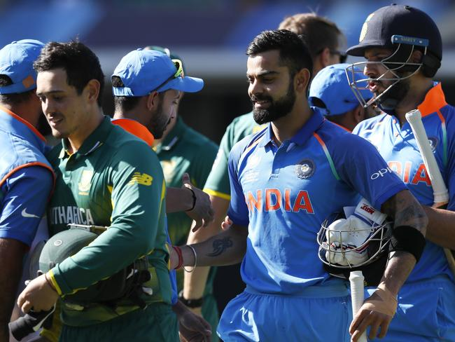 India's captain Virat Kohli, centre, and Yuvraj Singh smile after defeating South Africa.