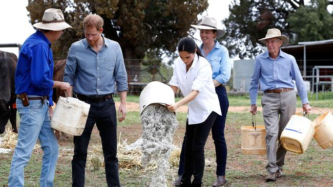 The couple get shown how to feed the stock on the Woodley farm in Dubbo. Picture: Chris Jackson/Getty Images